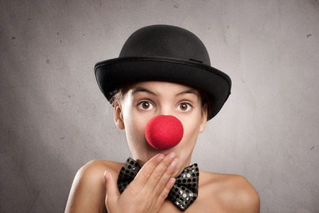 clown nose: portrait of surprised little girl with a clown nose