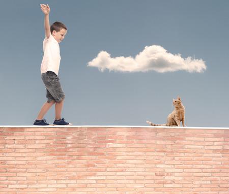 kleine jongen lopen in evenwicht op een muur Stockfoto