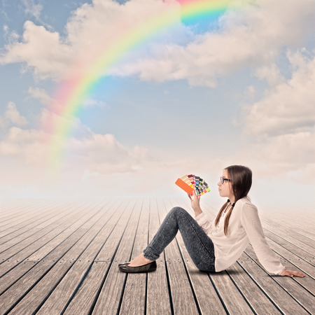 young girl holding a pantone palette on a wharf with rainbow in the sky photo