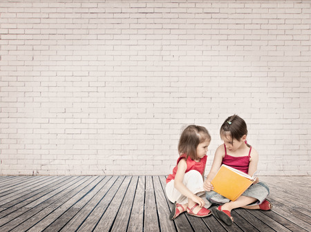 little girls reading a book sitting on a wood floor photo