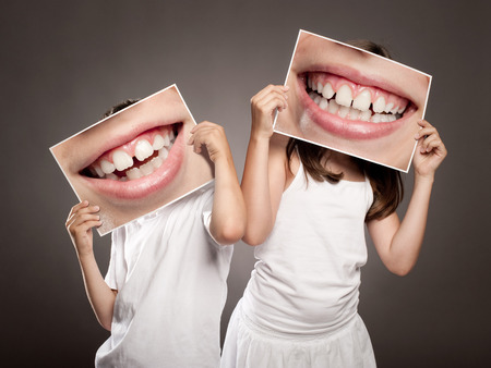 two children holding a picture of a mouth smiling Stockfoto