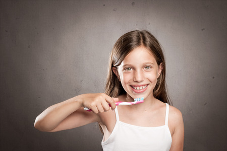 wash face: girl brushing her teeth on a gray background