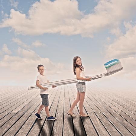 twee kinderen die een grote tandenborstel op een werf