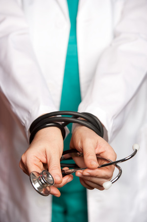 bound woman: female doctor tied by her stethoscope Stock Photo