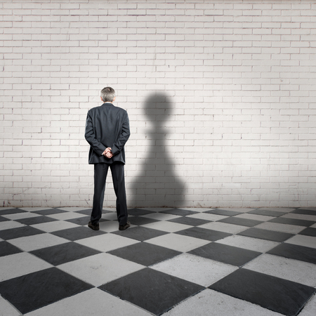 winner man: businessman with pawn shadow on a chess board