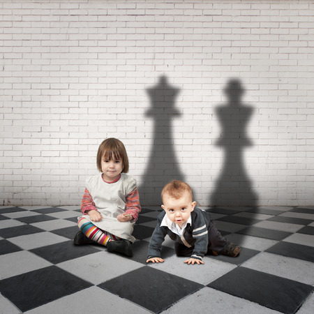 spoiled: child with king and queen shadows on a checkered floor Stock Photo
