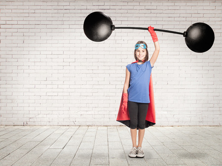 heavy weight: little girl superhero holding a heavy weight