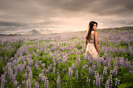 woman in field: young woman standing on a meadow at sunset