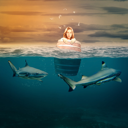 woman floating in a barrel surrounded by sharks