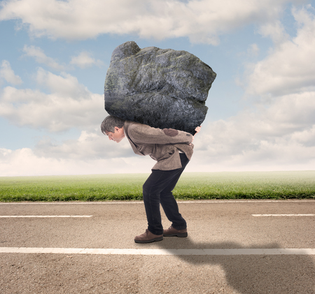 oppressed: businessman holding a big rock on a road