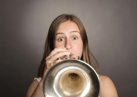 femme jouer de la trompette sur fond gris