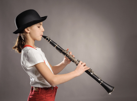 little girl playing clarinet on a gray background photo