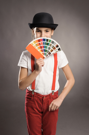 little girl holding a pantone palette on a gray background photo