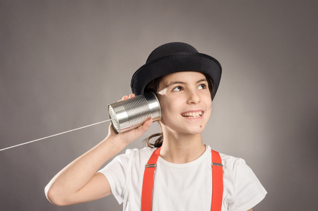 little girl using a can as telephone on a gray background photo