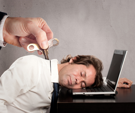winder: businessman with a key winder on his back sleeping on laptop