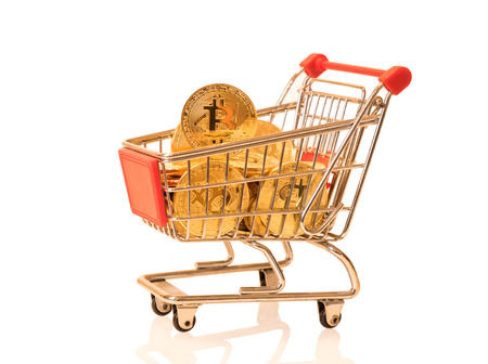 Shopping cart full of bitcoins on a white background