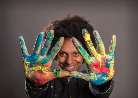 happy black woman with her hands painted on a gray background Archivio Fotografico