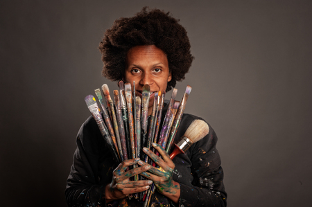 happy black woman holding paintbrushes on a gray background