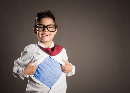 little boy opening his shirt like a superhero on a gray background Stockfoto