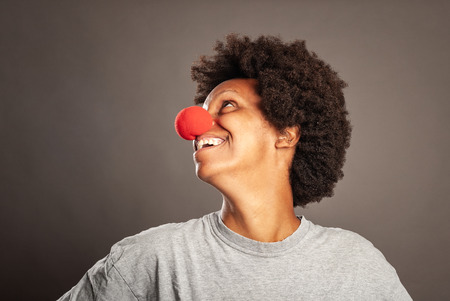 happy woman with a clown nose on a gray background