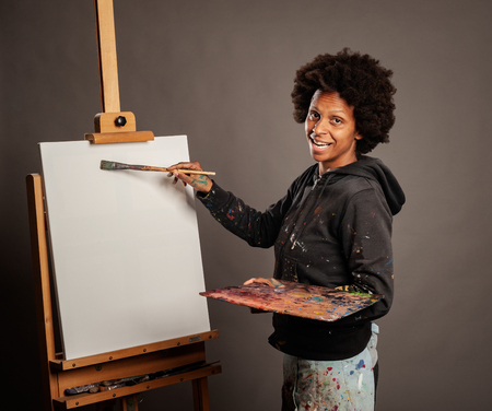 black woman painting on a gray background Stockfoto