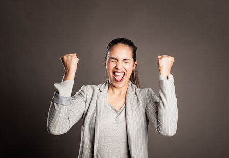 businesswoman celebrating being a winner on a gray background Stockfoto