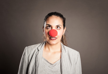 happy businesswoman with a clown nose on a gray background