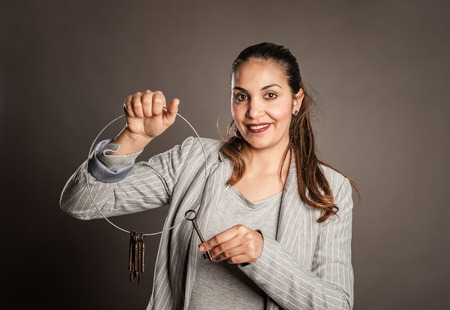 businesswoman holding old keys on a gray background
