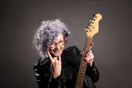 Close up portrait of beautiful older woman holding an electric guitar on a gray background