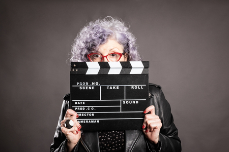 Close up portrait of beautiful older woman holding a movie clapper on a gray background