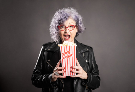 Close up portrait of beautiful older woman holding popcorn on a gray background