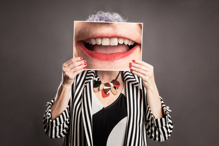 Close up portrait of beautiful older woman holding a picture of a mouth smiling on a gray background