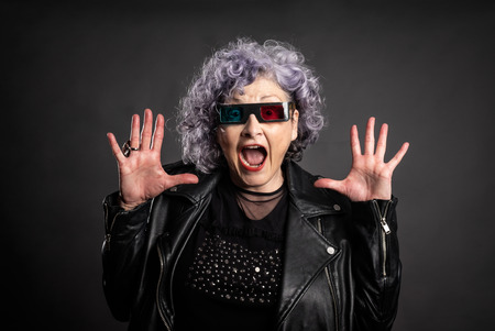 portrait of beautiful older woman wearing 3d glasses on a gray background