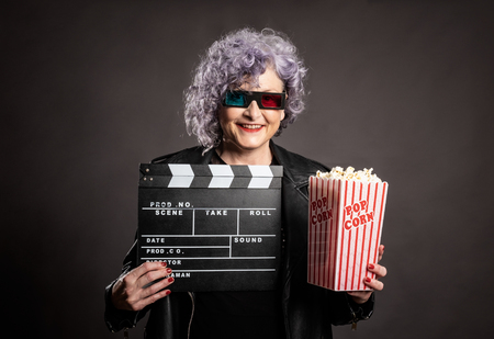 portrait of beautiful older woman holding popcorn and movie clapper on a gray background Stockfoto