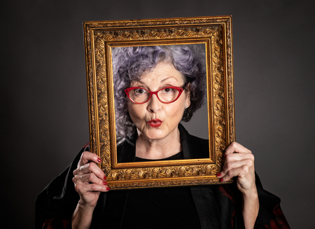 portrait of beautiful older woman holding a frame on a gray background
