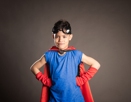 little boy wearing a superhero costume on a gray background Stockfoto