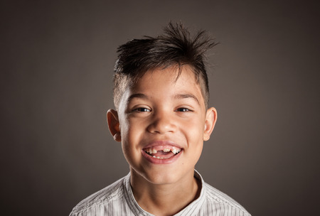 portrait of happy kid smiling on a grey background Stockfoto