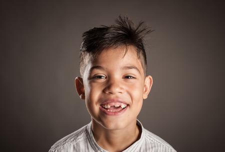 portret van een gelukkig kind dat lacht op een grijze achtergrond Stockfoto