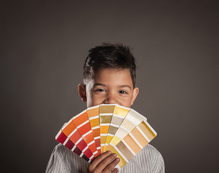 kid holding a pantone palette on a gray background Stock Photo