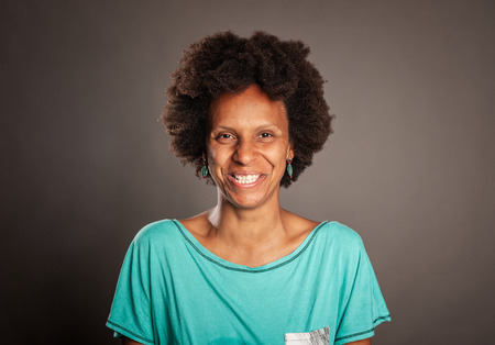 portrait of happy black woman smiling on a gray background