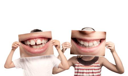 two children holding a picture of a mouth smiling isolated on white Stockfoto
