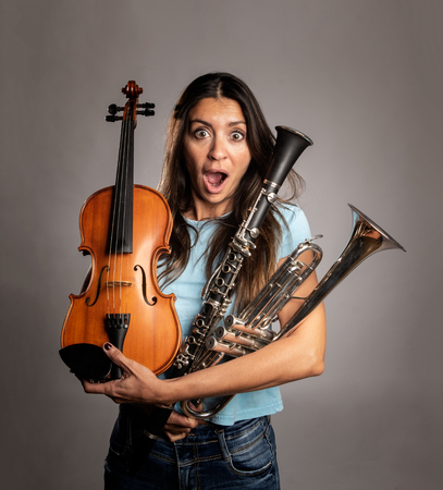 surprised woman holding musical instruments on a gray background Stockfoto