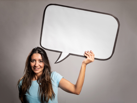 woman holding  a speech bubble on a gray background Stockfoto