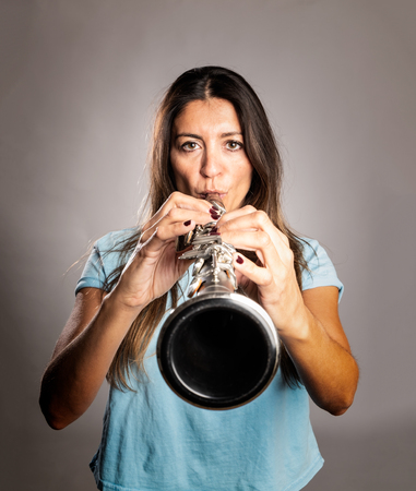 woman playing a clarinet on a gray background