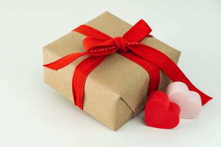 Close-up of gift box with red ribbon and two hearts on white background.