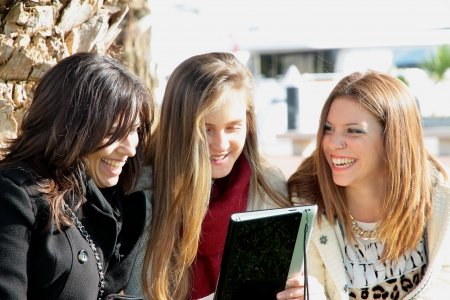 electronica: three pretty girls with a tablet  Stock Photo
