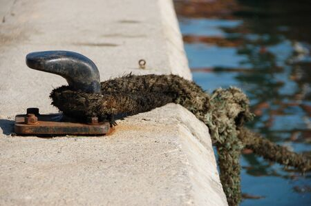 A rusty bollard in the dock with a tied rope.