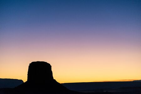 Sunset hues over the silhouette of a butte in Monument Valley 免版税图像