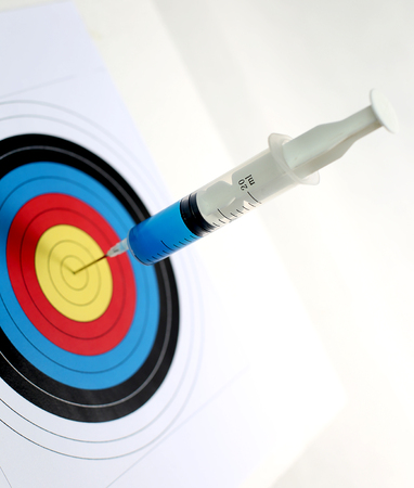 Precision medical syringes hit the bull's eye 스톡 콘텐츠