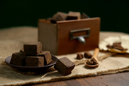 Brown sugar chunks in wooden boxes and plates 스톡 콘텐츠
